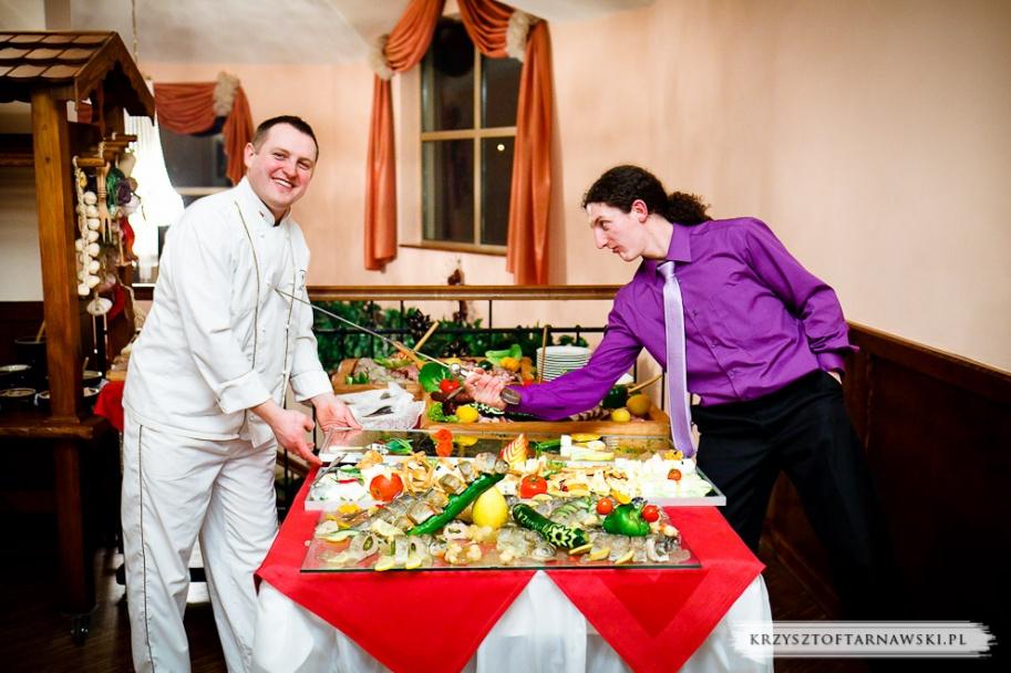 fotograf ślubny Kraków gość weselny podczas zabawy wbija miecz w brzuch kucharza