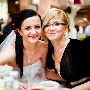 fotografia ślubna kraków pani młoda uśmiecha się do zdjęcia razem z druhną
