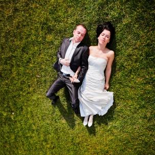 fotograf ślubny Kraków państwo młodzi podczas sesji plenerowej leżą w trawie i odpoczywają