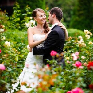 fotograf ślubny Kraków pani młoda obejmuje pana młodego podczas sesji plenerowej w ogrodzie botanicznym