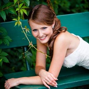 fotograf ślubny Kraków pani młoda uśmiecha się do zdjęcia leżąc na ławce w parku