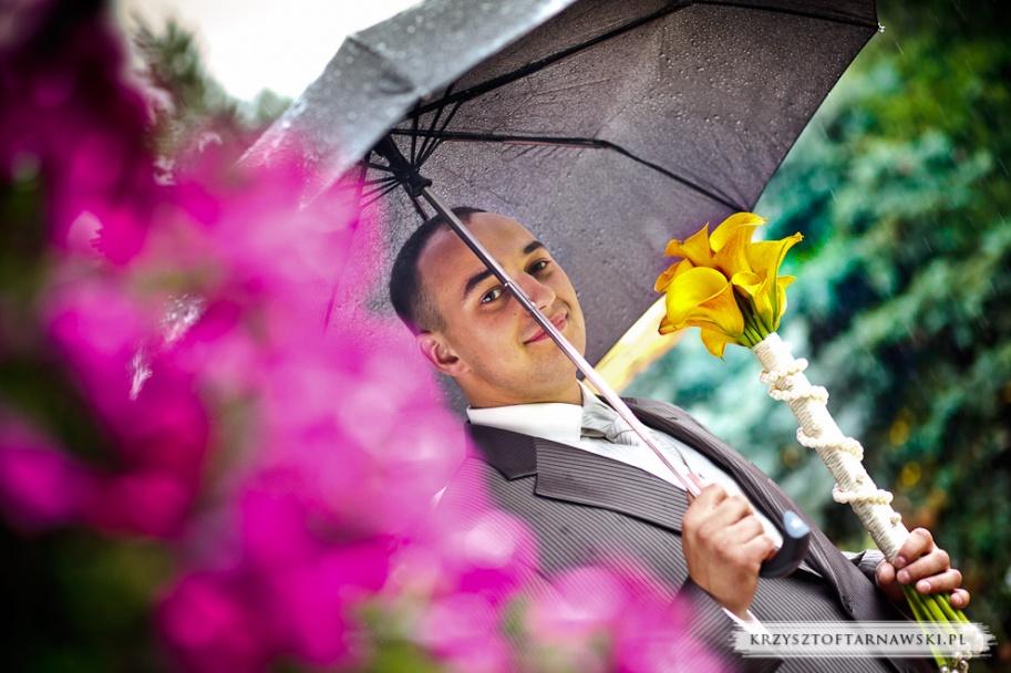 fotograf ślubny Kraków pan młody chorni się przed deszczem pod parasolem