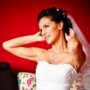 fotograf ślubny Kraków pani młoda poprawia włosy po założeniu welonu ślubnego
