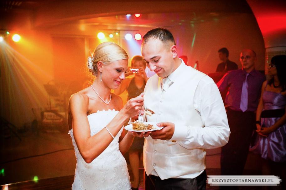 fotograf ślubny Kraków państwo młodzi próbują smaku ich ciasta weselnego