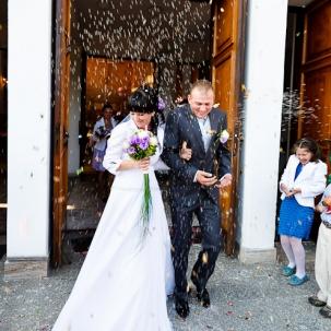 fotograf ślubny Kraków państwo młodzy przy wychodzeniu z kościoła obsypywani kwiatami