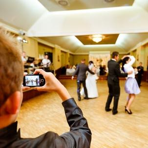 fotograf ślubny Kraków gość weselny robiący zdjęcie telefonem komórkowym bawiących się gości