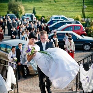 fotograf ślubny Kraków pan młody wnosi panią młodą na salę weselną
