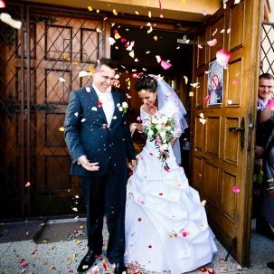 fotograf ślubny Kraków państwo młodzi przy wyjściu z kościoła obsypani ryżem