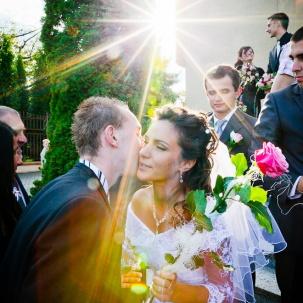 fotograf ślubny Kraków pani młoda w blasku słonca przyjmuje życzenia od gościa weselnego