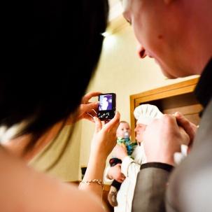 fotograf ślubny Kraków kucharz weselny trzymający dziecko państwa młodych podczas robienia pamiątkowego zdjęcia telefonem